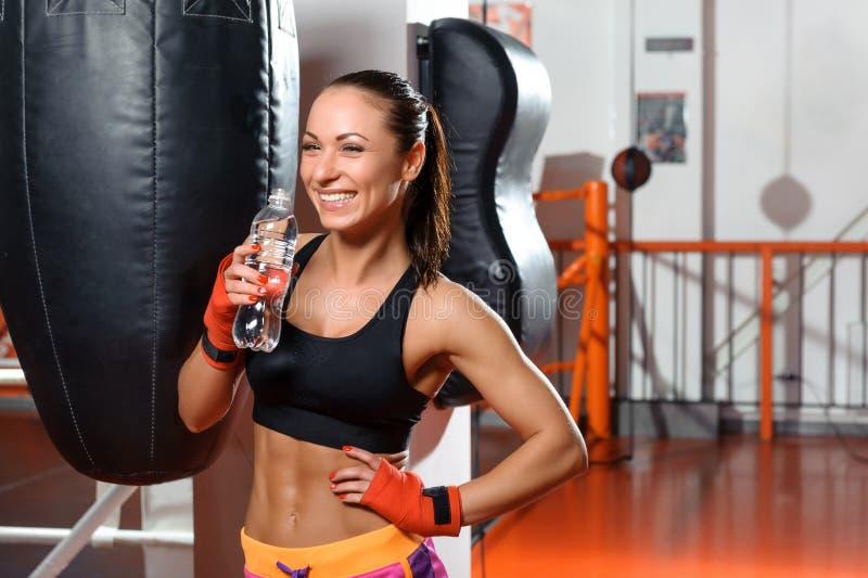 Het wijfje kickboxer drinkt water stock fotografie