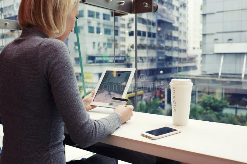 Het wijfje maakt het winkelen in Internet via digitale tablet, terwijl in koffie zit royalty-vrije stock afbeeldingen