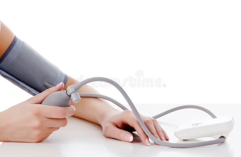 Het wijfje meet haar bloeddruk stock fotografie
