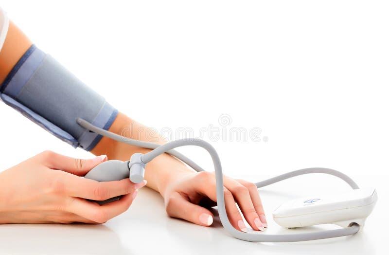 Het wijfje meet haar bloeddruk stock foto's