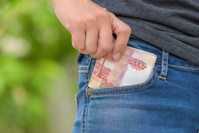 Het wijfje plukt de Roebelgeld van Rusland van zak met de hand stock afbeelding