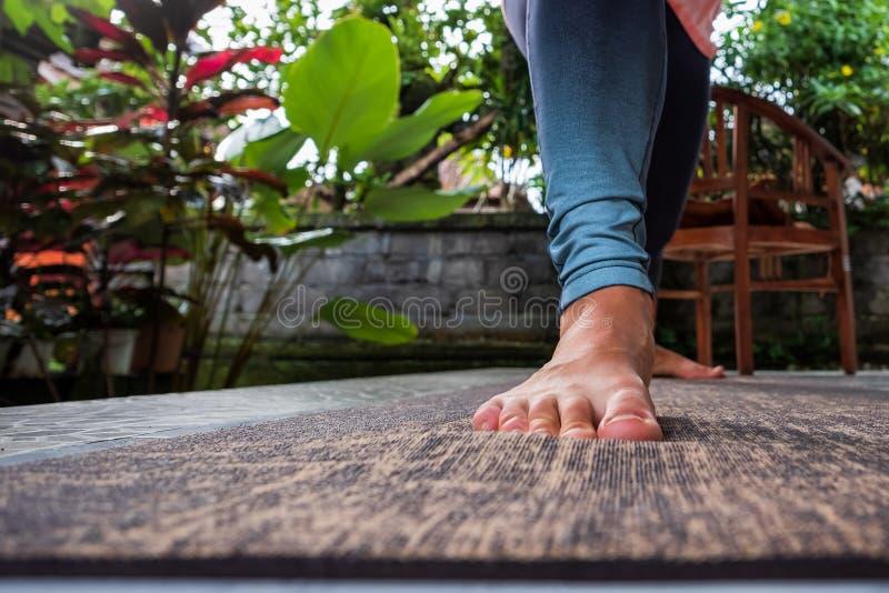 Het wijfje rekte blootvoets been in sportkleding, blauwe yogabroek voor het uitoefenen van yoga uit royalty-vrije stock fotografie