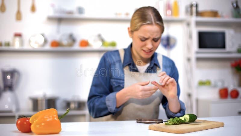 Het wijfje sneed vinger terwijl het snijden van komkommer, ongeval in keuken, huishoudenverwonding stock afbeeldingen