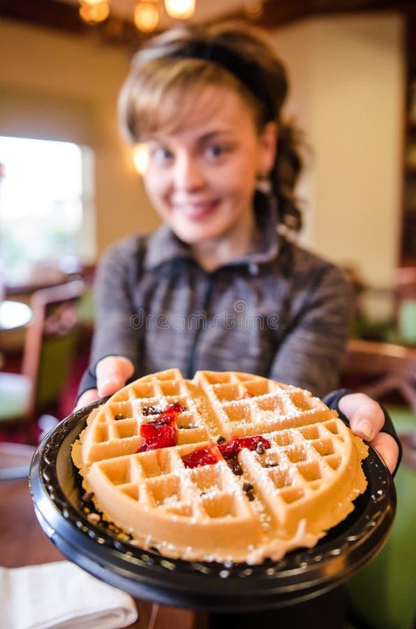 Het wijfje steunt een wafel van het ontbijtvoedsel met een vork Opzettelijk vage achtergrond met nadruk slechts op de wafel royalty-vrije stock foto's