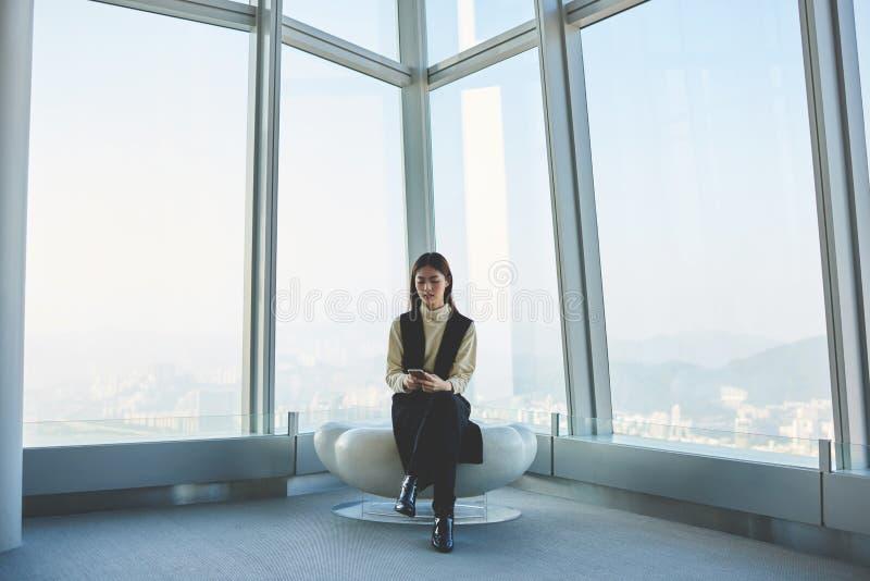 Het wijfje zit in bureaubinnenland tegen wolkenkrabbervenster met de stadsmening van New York stock fotografie