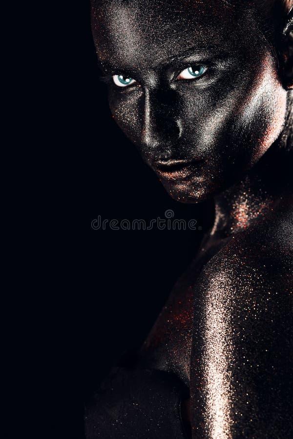 Het wijfje in zwarte verf met schittert stock foto's
