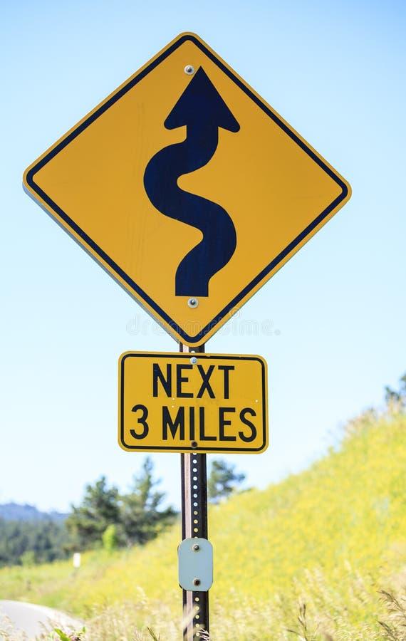 Het winden weg volgende 3 mijlen, verkeersteken stock foto