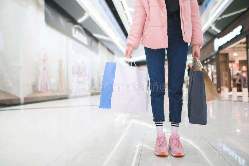 Het winkelen concept Een vrouw met pakketten in haar handen is in de wandelgalerij royalty-vrije stock fotografie