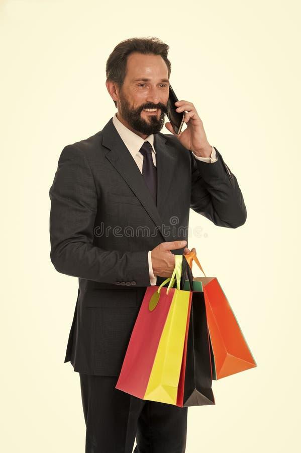 Het winkelen concept Gelukkige Mens met het winkelen zakken Het winkelen verslaafdenbespreking op mobiele telefoon Het omzetten v royalty-vrije stock foto's