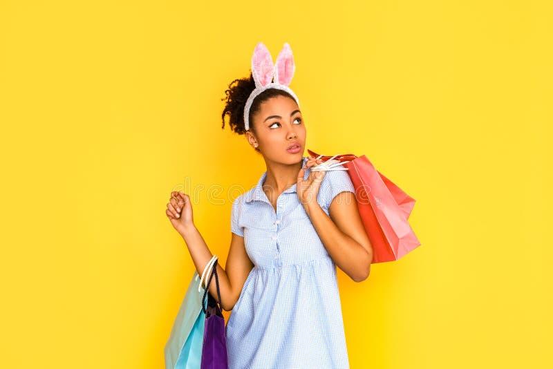 Het winkelen concept Jonge vrouw in leuke kleding en konijntjesoren status geïsoleerd op geel met zakken die opzij nieuwsgierig k stock foto