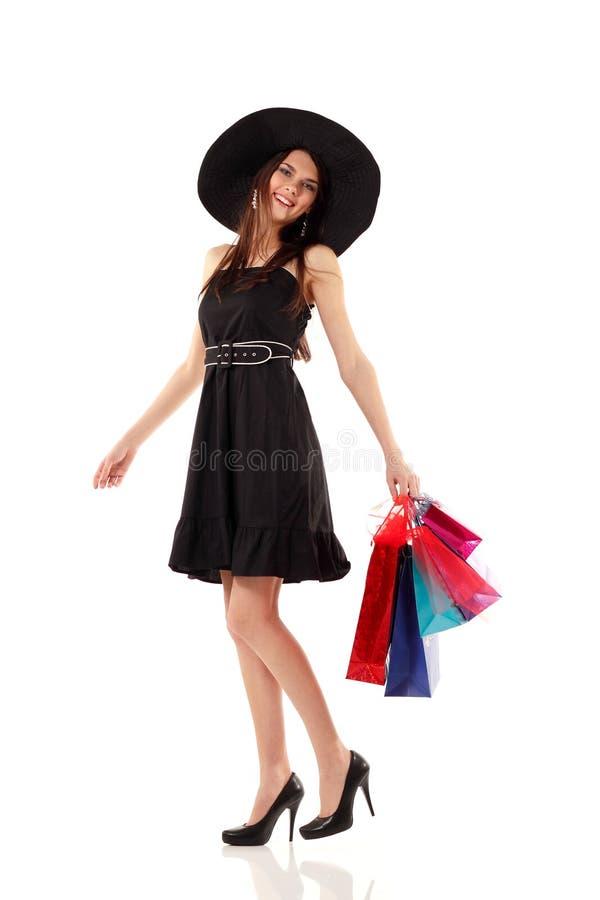Het winkelen jonge vrouw het glimlachen holdingszakken geïsoleerd o van gemiddelde lengte stock afbeeldingen
