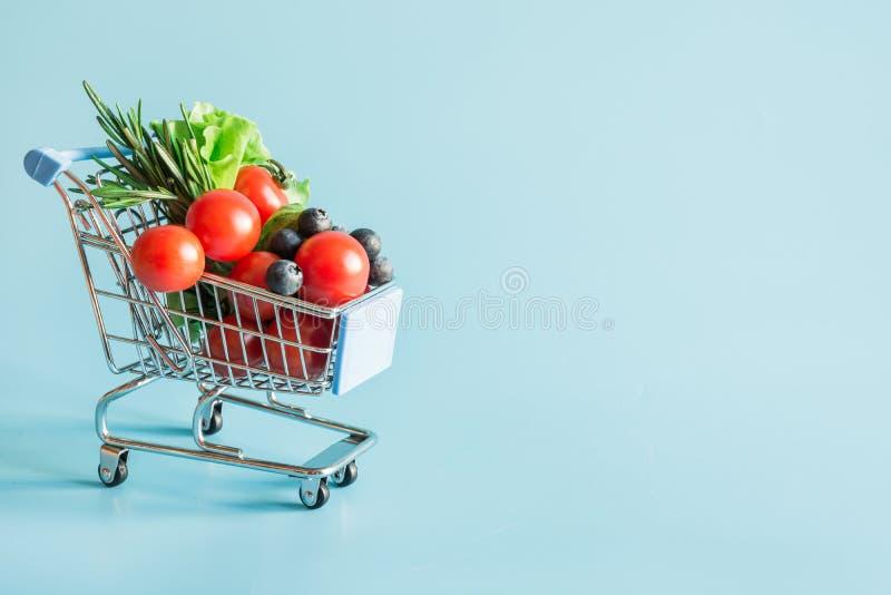 Het winkelen karretjehoogtepunt van verse die groentenkruidenierswinkels op blauw wordt ge?soleerd stock foto