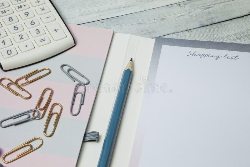 Het winkelen lijstconcept, calculator en potlood voor begrotingsaankopen, close-up royalty-vrije stock afbeeldingen