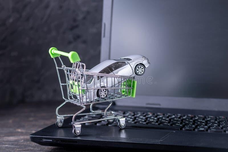 Het winkelen mand met auto op laptop toetsenbord op donkere achtergrond Concept online het winkelen voertuigen op Internet stock foto
