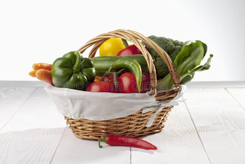 Het winkelen mand met diverse verse organische groenten op witte houten achtergrond wordt gevuld die royalty-vrije stock afbeelding