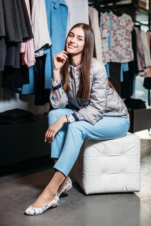 Het winkelen, manier, stijl, verkoop, het winkelen, zaken en mensen concepten mooie gelukkige jonge vrouw in kledingsopslag Zaken royalty-vrije stock afbeelding