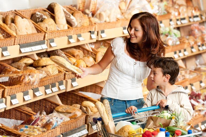 Het winkelen reeks - Bruine haarvrouw met kind stock afbeelding