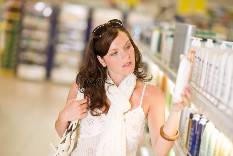 Het winkelen schoonheidsmiddelen - de vrouw kiest shampoo stock afbeeldingen