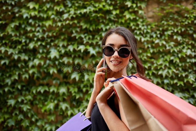 Het winkelen Sluit omhoog portret van jong aantrekkelijk tan-gevild Kaukasisch meisje in zonnebril en de zwarte partij van de kle royalty-vrije stock afbeelding