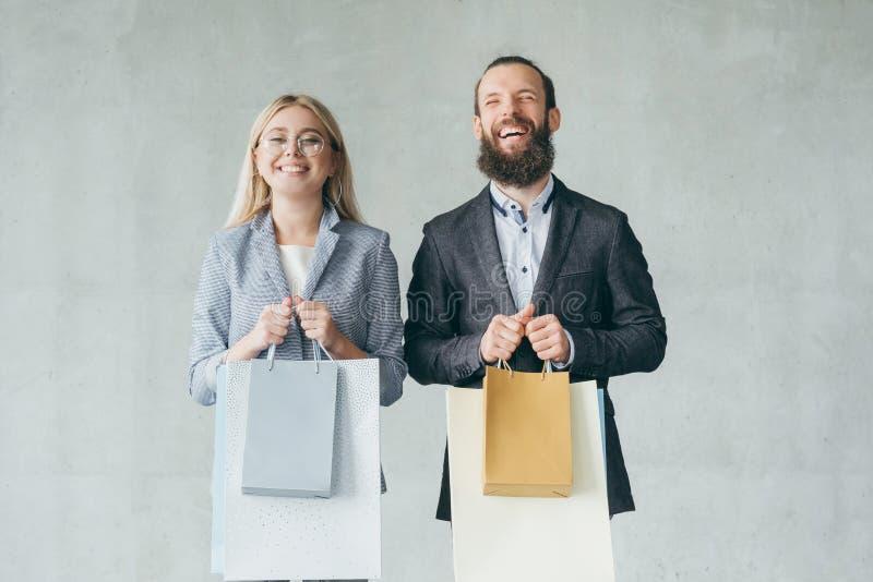Het winkelen therapie de gelukkige het glimlachen zakken van de paargreep royalty-vrije stock fotografie