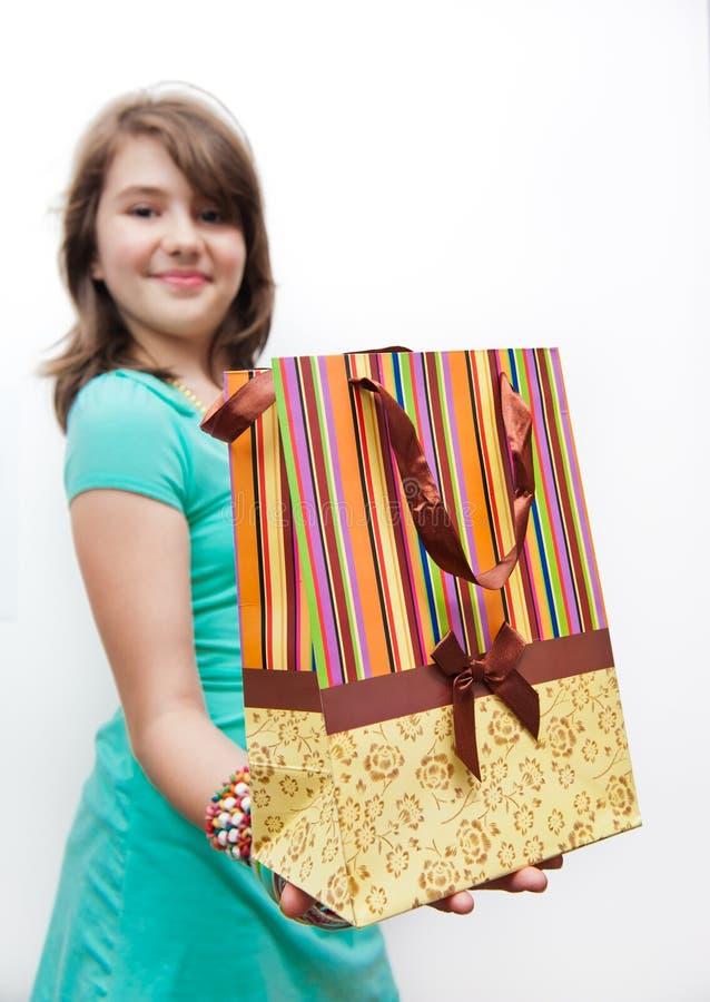 Het winkelen tienermeisje het glimlachen holding het winkelen zakken. stock foto