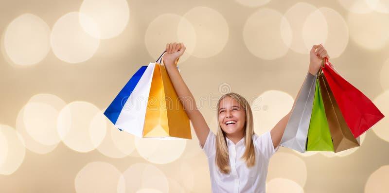 Het winkelen, vakantie en toerismeconcept - jong meisje met het winkelen zakken over beige achtergrond stock afbeelding