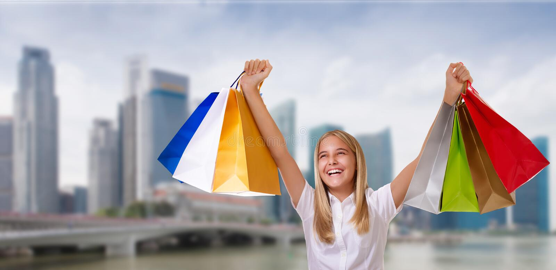 Het winkelen, vakantie en toerismeconcept - jong vrolijk meisje met het winkelen zakken over stadsachtergrond stock afbeelding