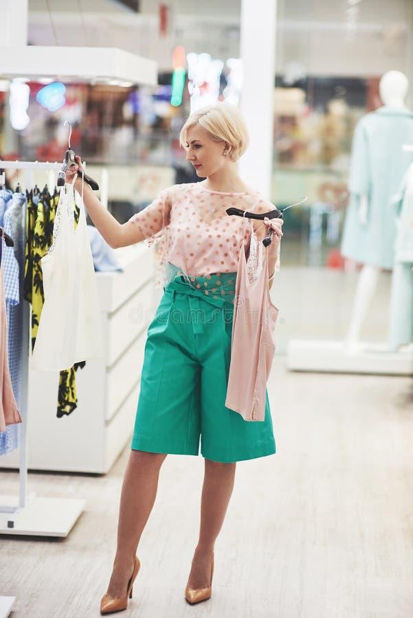 Het winkelen van de vrouw kleren Klant die kleding binnen in opslag bekijken Mooi gelukkig glimlachend Aziatisch Kaukasisch wijfj royalty-vrije stock afbeeldingen