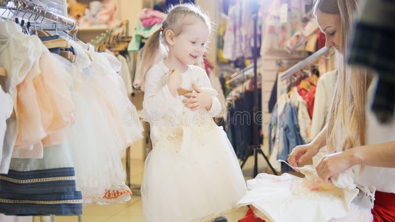 Het winkelen voor jonge geitjes - leuk meisje met mama het kopen kleding in opslag van jonge geitjeskleren stock fotografie