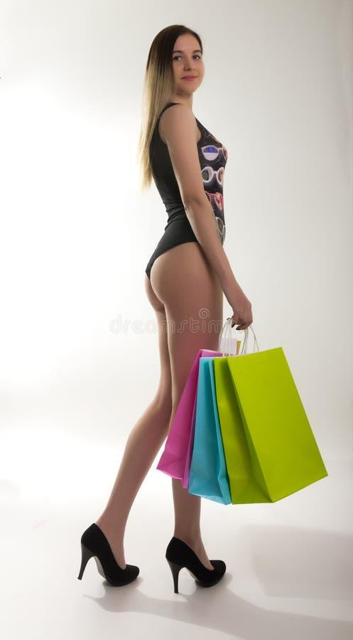 Het winkelen vrouwenholding het winkelen zakken Close-up die van mooie vrouwenbenen in een badpak en hoge hielen, kleurrijk houde royalty-vrije stock foto