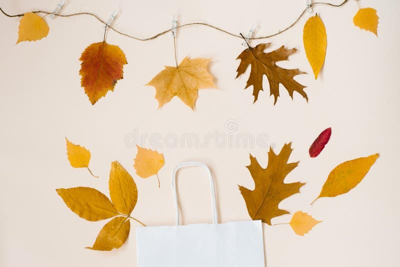 Het winkelen Witboekzak met gevallen bladeren die uit het gluren, geïsoleerd op beige achtergrond, de herfstverkoop en kortingen  stock foto's
