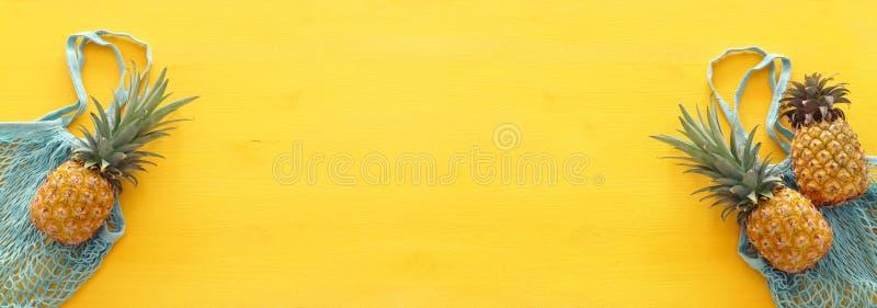 Het winkelen zak met ananas over gele houten achtergrond Strand en tropisch thema Hoogste mening stock afbeelding