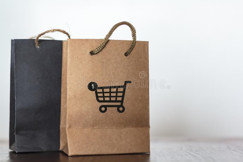 Het winkelen zakken met karpictogram op houten lijst Commerciële zaken, detailhandel, online het winkelen concept stock afbeeldingen
