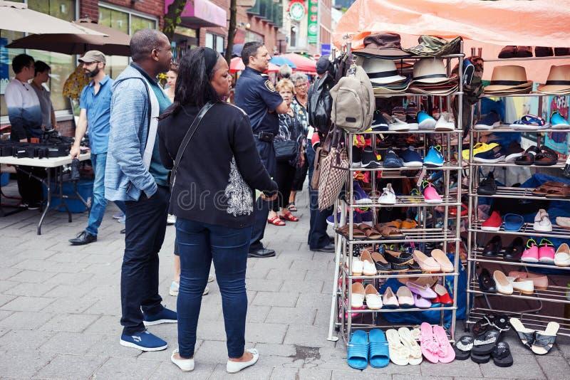 Het winkelende Amerikaanse paar die van Afro de producten op de teller van een openluchtmarkt bij Chinatown in Montreal, Quebec,  stock foto