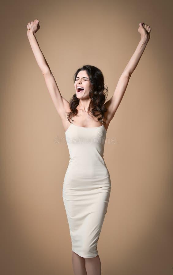 Het winnen, succes, en het levensdoelstellingen concept De jonge vrouw met wapens in lucht het geven beduimelt omhoog stock foto