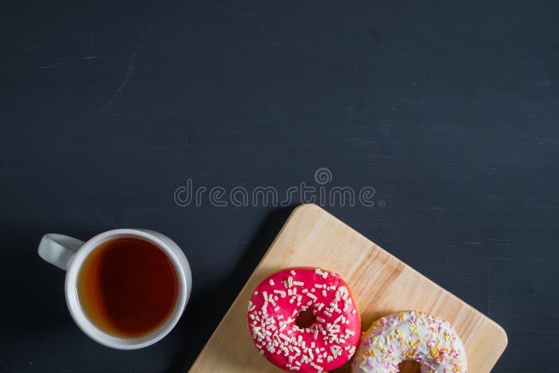 Het wit, doorboort verglaasd donuts met kop thee op zwarte houten achtergrond stock afbeelding
