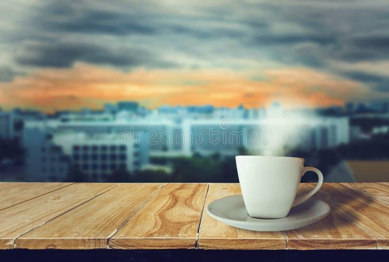 Het wit van de koffiekop op houten lijst met rook, met cityscape zonsondergangachtergrond wordt geplaatst die, die en zich met wa royalty-vrije stock foto's