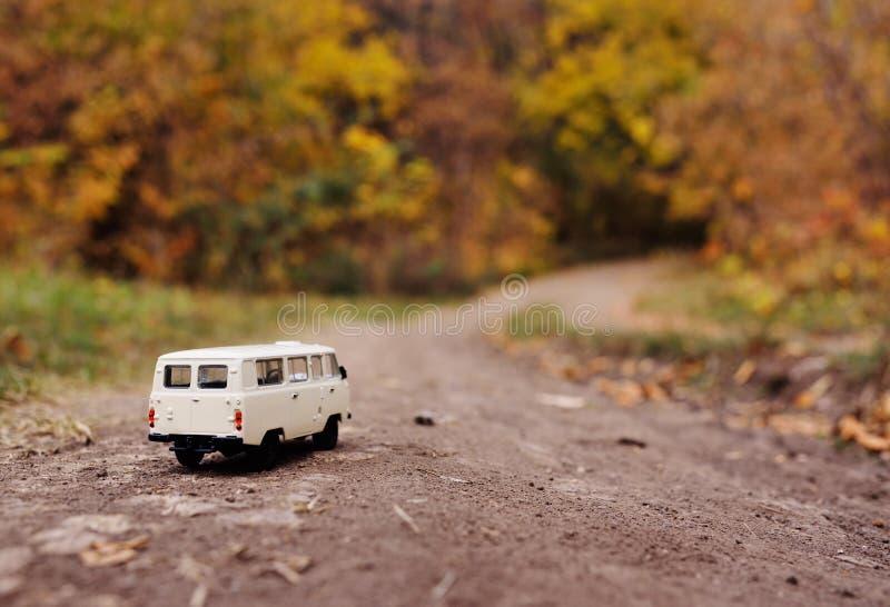 Het wit weinig stuk speelgoed auto berijdt op de weg tegen de achtergrond van de herfst gele bomen royalty-vrije stock afbeeldingen
