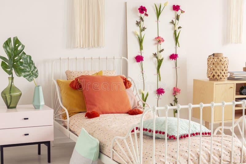 Het witmetaalbed met kleurrijke hoofdkussens en doted beddegoed in het elegante binnenland van de bohoslaapkamer stock fotografie