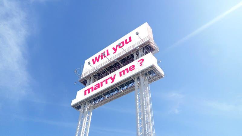 Het witte aanplakbord op duidelijke blauwe hemel met tekst verwoording zal u me huwen? Voor Valentijnskaarten, huwelijksgebeurten stock afbeelding