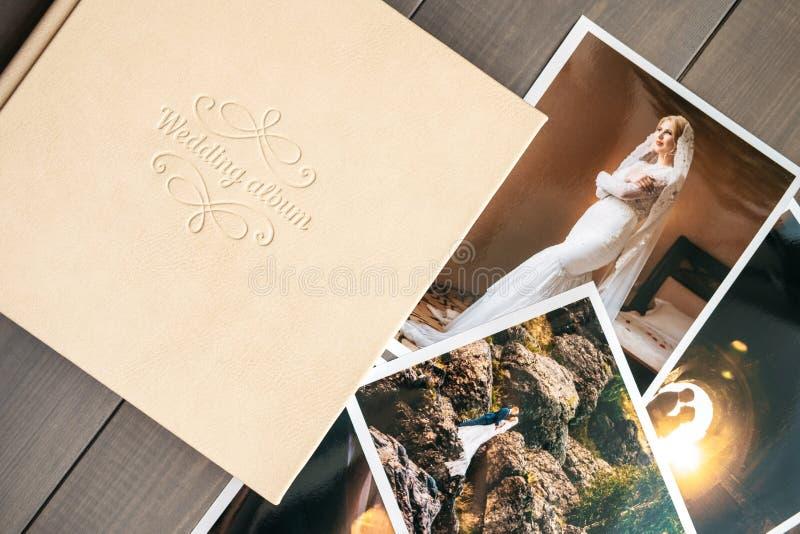 Het witte album van het leerhuwelijk en gedrukte foto's met de bruid en de bruidegom stock foto