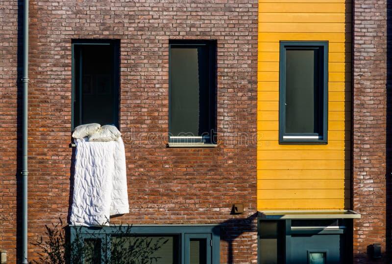 Het witte Algemene hangen buiten het venster, die het bedlinnen, typische Nederlandse Architectuur ventileren royalty-vrije stock foto