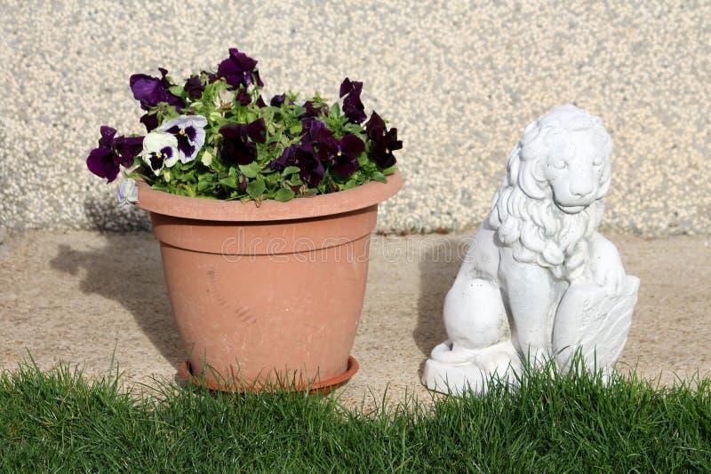 Het witte concrete beeldhouwwerk van het machtige schild van de leeuwholding naast ceramische die bloempot met tweekleurig wild v stock fotografie