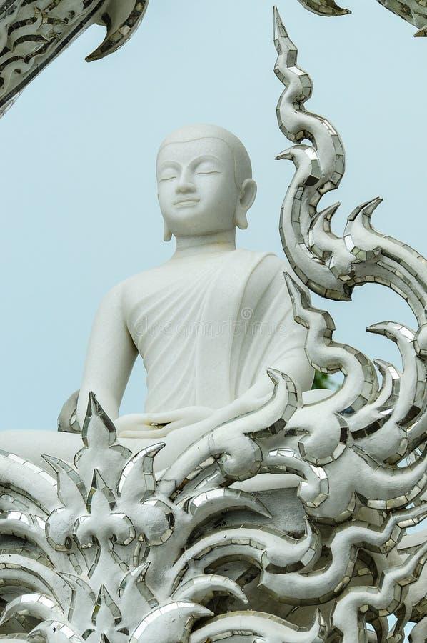Het witte die beeld van Boedha in de tempel wordt verfraaid stock afbeeldingen