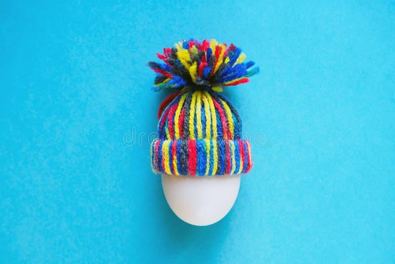 Het witte ei in gebreide wol kleurde hoed op blauwe achtergrond, Pasen-concept stock afbeelding