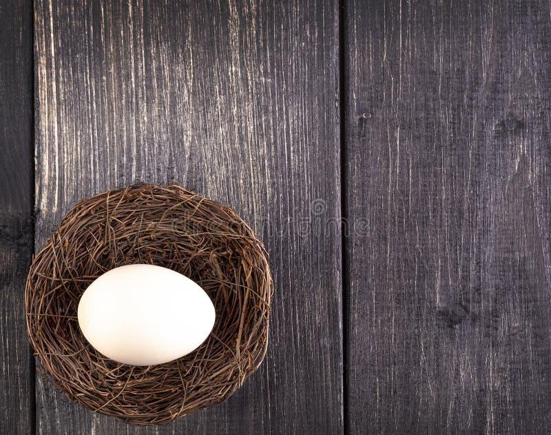 Het witte ei op het nest op de oude houten achtergrond stock foto