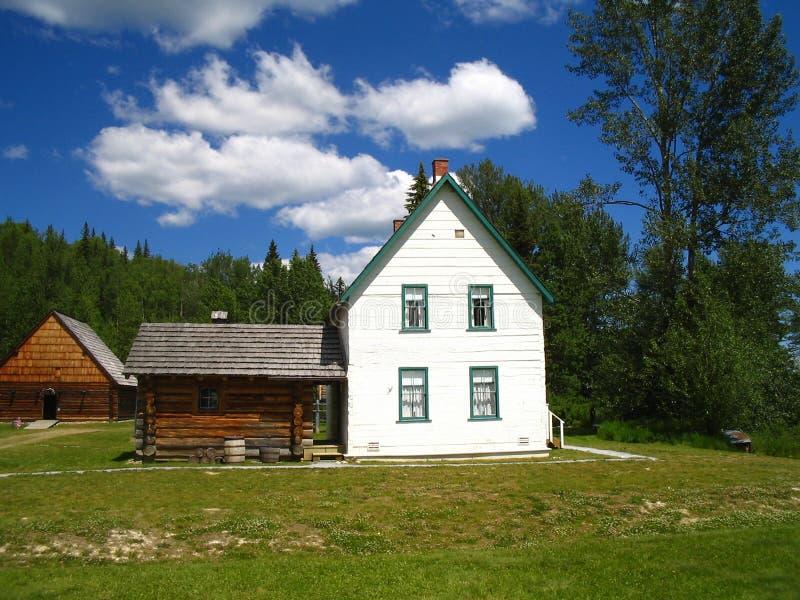 Het witte gezaagde huis van het logboek oudere landbouwbedrijf stock fotografie