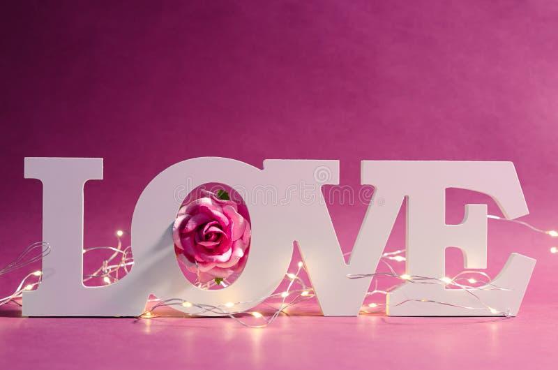 Het witte houten en geleide licht van de liefdetekst met roze nam op houten achtergrond toe royalty-vrije stock foto