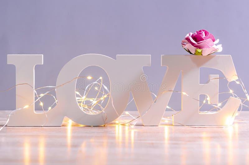 Het witte houten en geleide licht van de liefdetekst met roze nam toe stock fotografie