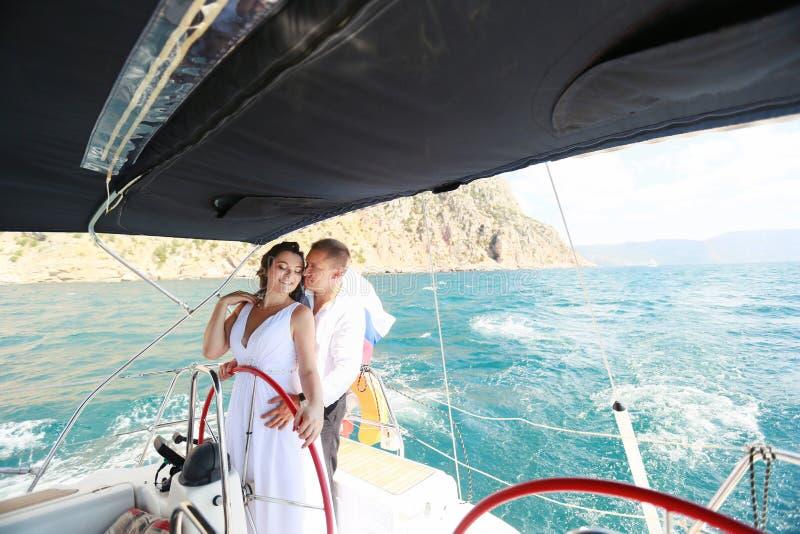 het witte jacht met zeilreeks gaat langs het eiland op een hete dag Blauwe overzees, blauwe hemel crimea aan boord van een jong p royalty-vrije stock foto's